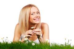 Frau auf Gras mit Blumen Stockfotografie