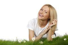Frau auf Gras mit Blumen Lizenzfreie Stockbilder
