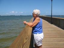 Frau auf hölzernem Pier über Wasser Stockbild