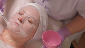 Frau auf Hautverjüngungsverfahren in der Cosmetologymitte Der Kosmetiker mithilfe einer weißen Bürste wendet das Gel durch an stock footage