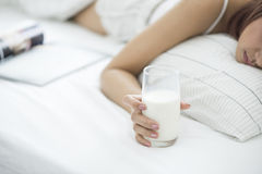 Frau auf ihrem Bett mit einem Glas von Milch von in der Hand, Tiefe und von flachem Fokus auf Glas Milch lizenzfreie stockfotos