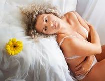 Frau auf ihrem Bett zu Hause Lizenzfreie Stockbilder