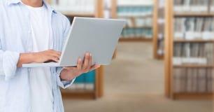 Frau auf Laptop in der Bibliothek Lizenzfreie Stockfotografie