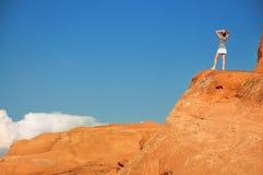 Frau auf orange Felsen Stockbilder