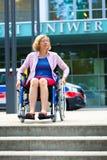 Frau auf Rollstuhl und Schritten Stockbild