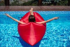 Frau auf rotem Ruhesessel im Pool stockfotografie