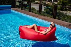 Frau auf rotem Ruhesessel im Pool lizenzfreie stockfotos