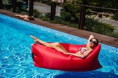 Frau auf rotem Ruhesessel im Pool lizenzfreie stockbilder