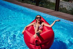 Frau auf rotem Ruhesessel im Pool stockbild