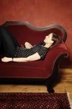 Frau auf rotem Sofa serie Lizenzfreies Stockfoto