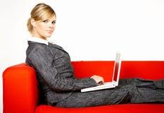 Frau auf roter Couch Lizenzfreie Stockfotografie