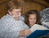 Frau auf Sauerstoff liest zum kleinen Mädchen stockfotografie