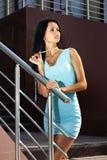 Frau auf Schritten im blauen Kleid Stockfoto
