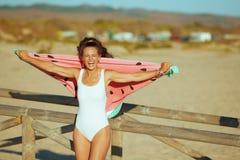 Frau auf Seeküste am Abend lustiges Wassermelonentuch halten stockfotos