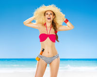 Frau auf Seeküste mit dem Sonnenschutzmittel, das oben auf Kopienraum schaut Stockbilder