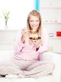 Frau auf Sofa Kuchen zu Hause essend Lizenzfreie Stockfotografie