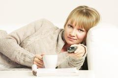 Frau auf Sofa mit Fernsteuerungs Stockbilder