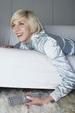 Frau auf Sofa With Remote Control Stockfotografie