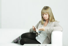Frau auf Sofalesebuch Stockbilder