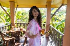 Frau auf Sommer-Terrassen-Griff-Handgetränk-Orangensaft, glückliches lächelndes Mädchen in der Morgen-freundlichen Geste draußen stockfotografie