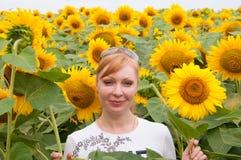 Frau auf Sonnenblumenfeld Stockfotografie
