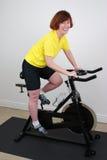 Frau auf spinnendem Fahrrad Lizenzfreie Stockbilder