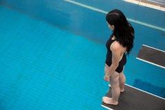 Frau auf Sprungbrett am allgemeinen Swimmingpool Lizenzfreies Stockfoto