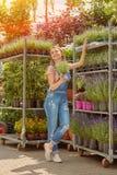 Frau auf Stand mit Blumen Lizenzfreies Stockfoto