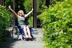 Frau auf steigenden Händen des Rollstuhls oben Stockbild