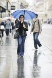 Frau auf Straße mit Regenschirm Stockbild