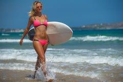 Frau auf Strand mit Surfbrett Stockbilder