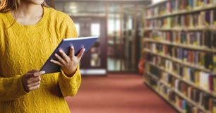 Frau auf Tablette in der Bibliothek Stockbild