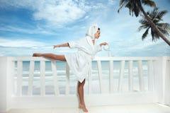 Frau auf Terrasse über Seeansicht Stockfotografie