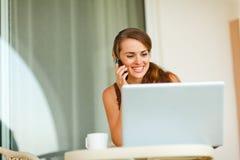 Frau auf Terrasse mit sprechendem Handy des Laptops Lizenzfreie Stockfotos