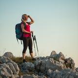 Frau auf Trekking - schönes blondes Mädchen, das auf Bergen wandert stockbild