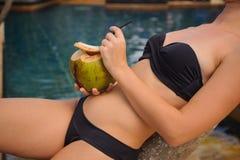 Frau auf trinkender Kokosnuss der Palme Stockfoto