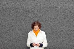 Frau auf Wand mit smartphone stockfotografie