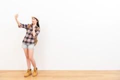 Frau auf weißem Hintergrund unter Verwendung des Handys Stockbild