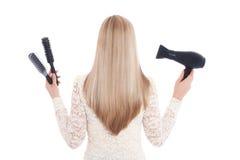Frau auf weißen Hintergrundholdingbürsten und einem hairdryer ablage Stockbild