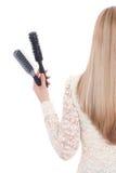 Frau auf weißen Hintergrundholdingbürsten und einem hairdryer ablage Lizenzfreie Stockfotos