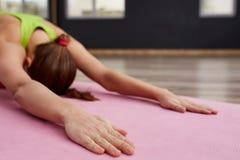Frau auf Yogaklassen-Innennahaufnahme von Händen in entspannender Haltung Stockfotografie