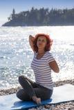 Frau Ausführungsjoga auf Seeküste Lizenzfreies Stockfoto