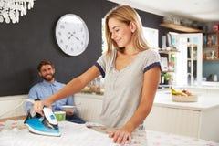 Frau bügelt Hemd, während Mann Frühstück isst Lizenzfreies Stockbild