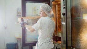 Frau backt auf Handelsküche - Züge das Brot vom Ofen stockbild