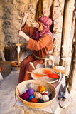 Frau bearbeitet spinnendes Rad der altmodischen Wollen Lizenzfreie Stockbilder