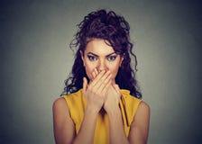 Frau bedeckt ihren Mund mit den Händen Stockfotografie