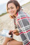 Frau bedeckt mit Decke unter Verwendung des Tablet-PCs am Strand Lizenzfreies Stockbild