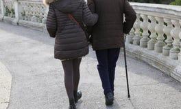 Frau begleitet den älteren Herrn mit Spazierstock Stockbilder