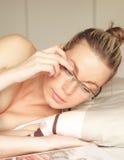 Frau begrenzt auf liegenmesswert des Betts Stockfotografie