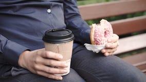 Frau beißt Donut und trinkenden Kaffee stock video footage
